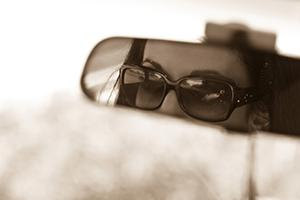 Woman in rear-view mirror of car