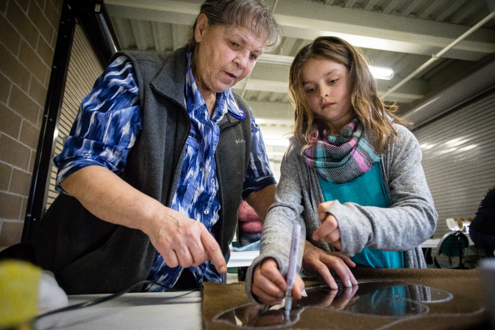 A teacher assists a young girl in a class during the Sewing & Stitchery Expo.