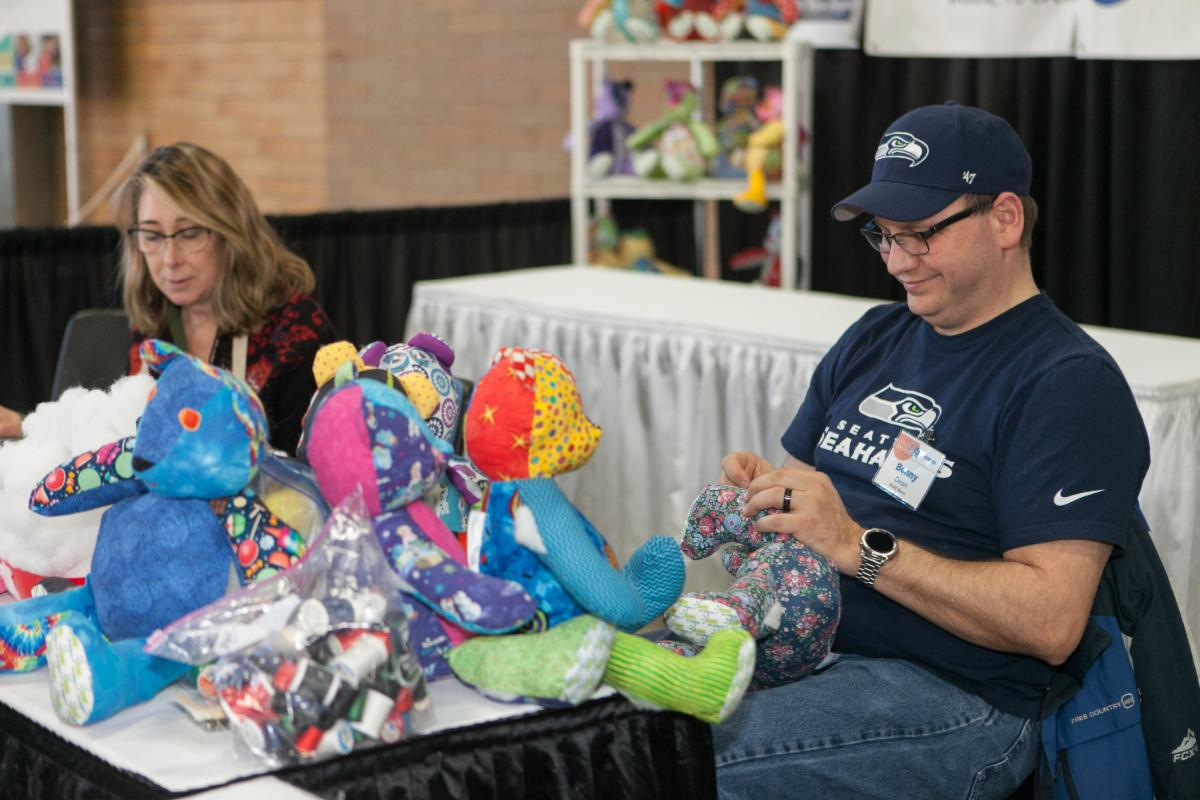 Volunteers at the 2019 Sewing & Stitchery Expo make Rare Bears for children.