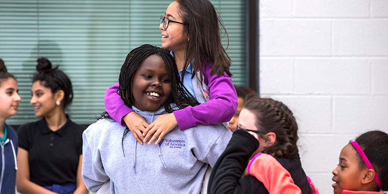 Photo of student carrying another student on her back, both smiling