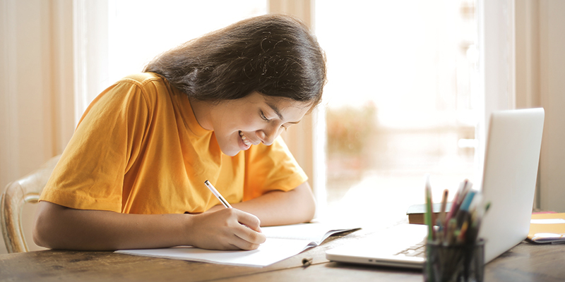 Student sits and writes on paper while in front of laptop while smiling