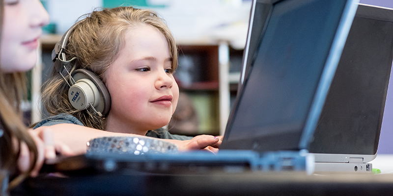 Student wears headphones smiling while looking at laptop