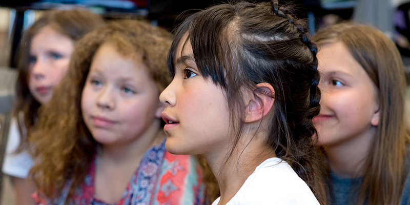 Student sits among classmates looking upward