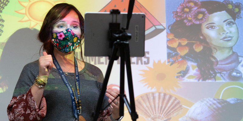 Teacher wearing a mask presents in front of whiteboard while recording on tablet
