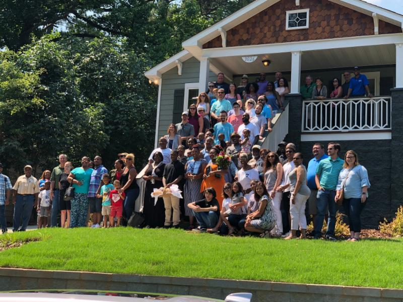 Employees and future homeowners standing in front of habitat house