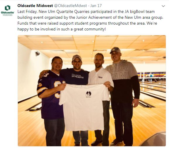 Four employees at a bowling alley holding up a t shirt