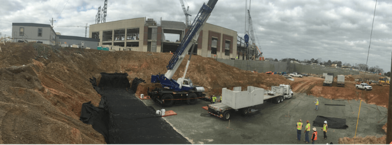 Construction site with crane lifting concrete and workers walking