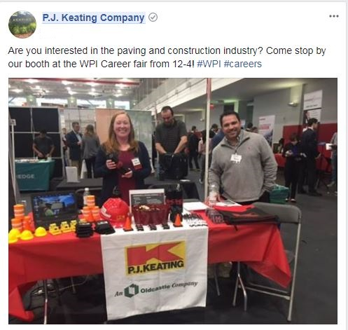 Smiling employees behind a table at a job fair