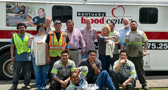 Employees in front of a blood drive truck