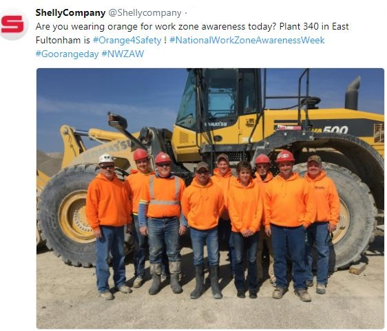 Employees wearing orange  in front of heavy equipment