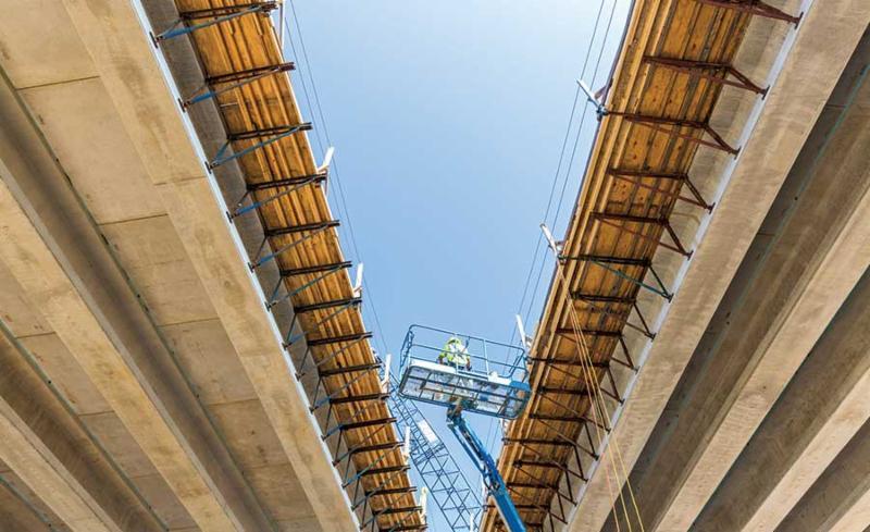 Crew member in a crane under an overpass
