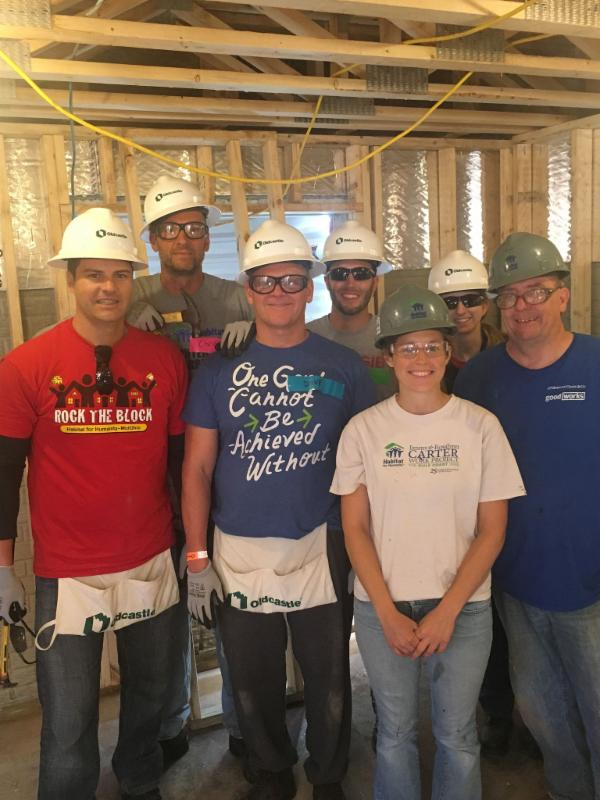 7 volunteers in hardhats inside house structure