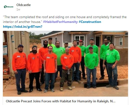 Employees in matching t shirts standing outside habitat for humanity house
