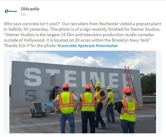 Employees in hard hats standing in front of huge concrete sign