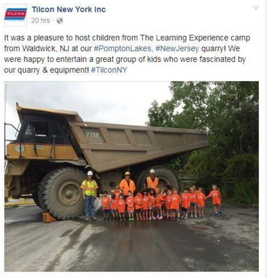 Children stanindg in front of a haul truck