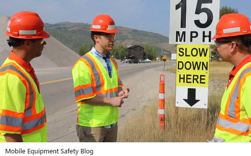 Three people in hard hats and safety vests standing by a traffic sign with a quarry in the background