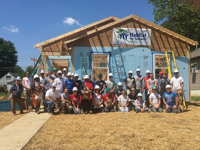 Volunteers outside habitat for humanity house in progress