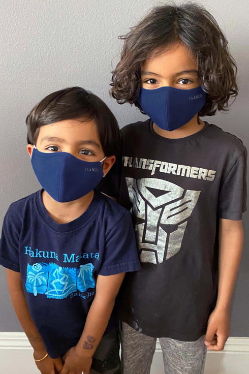 a taller child and a shorter child with dark hair and light brown skin stand together wearing navy blue masks and black tee shirts with graphics on the fronts