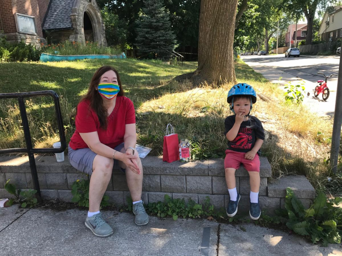 Small boy wearing red shorts black Raptors shirt and bicycle helmet sits to the right of white woman with long dark hear wearing a read shirt and rainbow mask with a jar and a red bag on the retaining wall between them