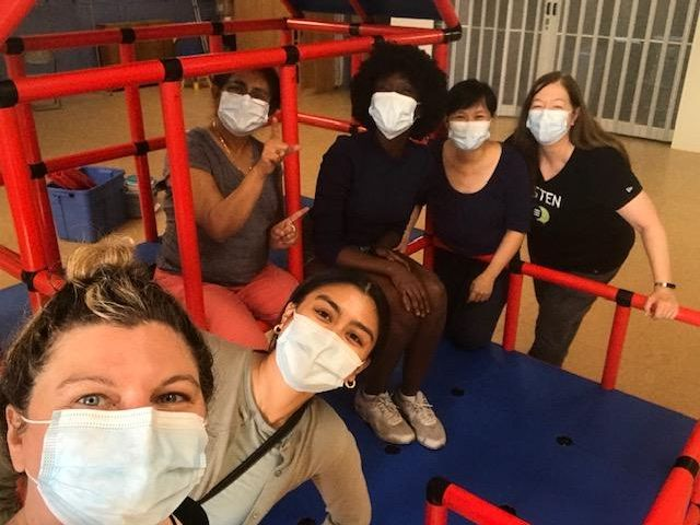 a group of racially diverse people wearing masks gather around a red plastic children's climbing apparatus