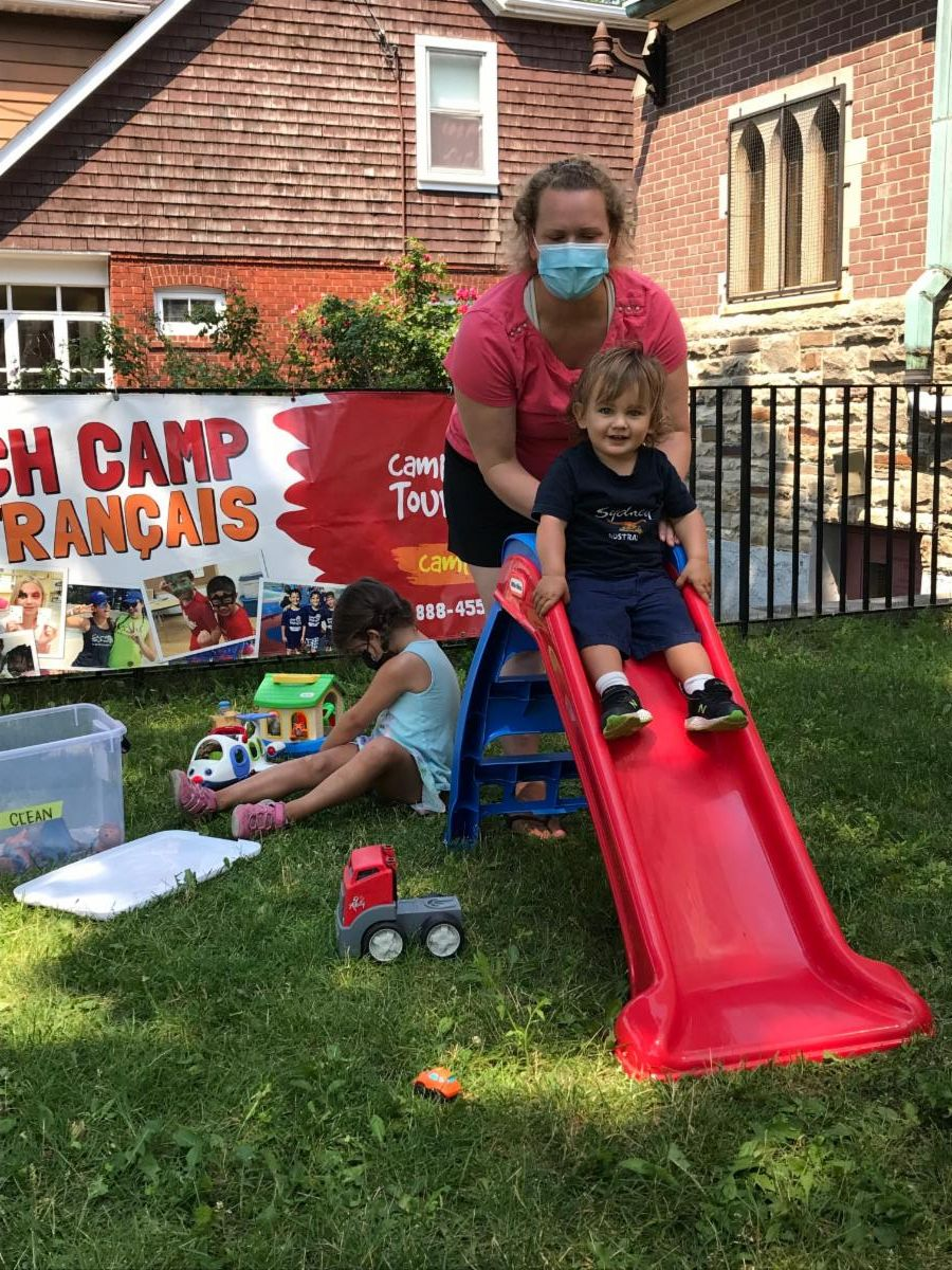 a parent wering a mask holds a child on top of a small toddler slide  while another child plays next to them