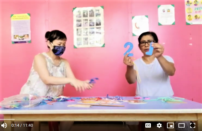 Againist a pink background an Asian person with dark hair and a dark face mask sits to the left at a blue table holding crafting materials next to a brown person with dark hair weaing a white tee shirt seated at the blue table with arms extended