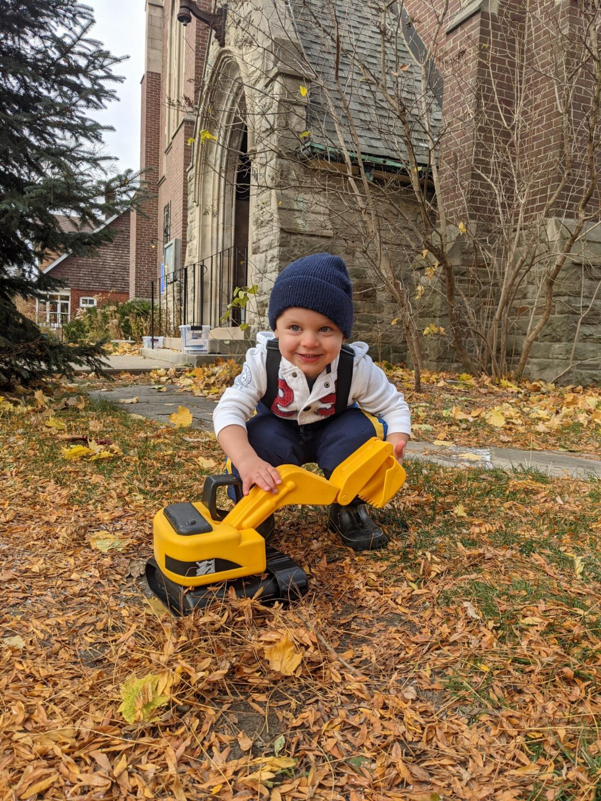 White child wearing a winter hat and show pants holds a yellow toy digger while sqatting on the ground outside a builiding.
