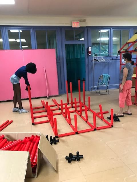 two people arranging red plastic tubs to create a base for an indoor climbing apparatus for children
