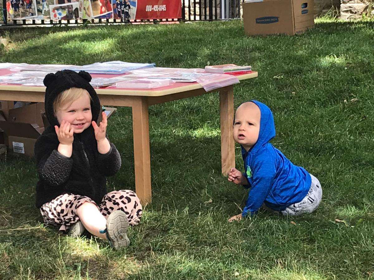 Two white toddlers sitting on the grass with one toddler uncovering their eyes and the baby looking at the camera