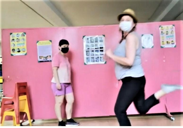 in the foreground a white person with dark braids and a hat wearing a white face mask jumps up with one foot extended behind while on a pink background an Asian person with dark hair and a dark face mask stands