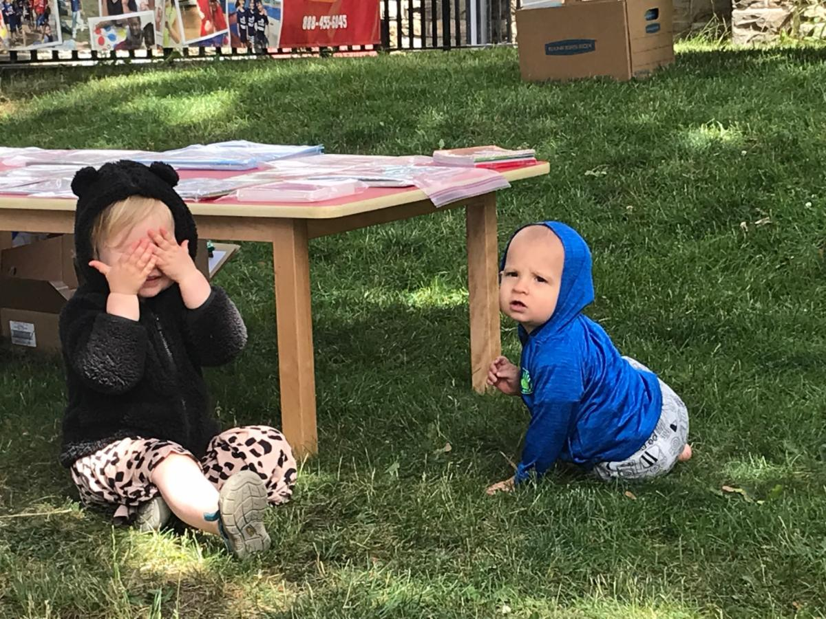 Two white toddlers sitting on the grass with one toddler covering their eyes and the baby looking at the camera