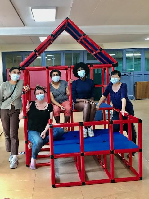 five people of various racial backgrounds wearing masks sit together  a red indoor climbing apparatus