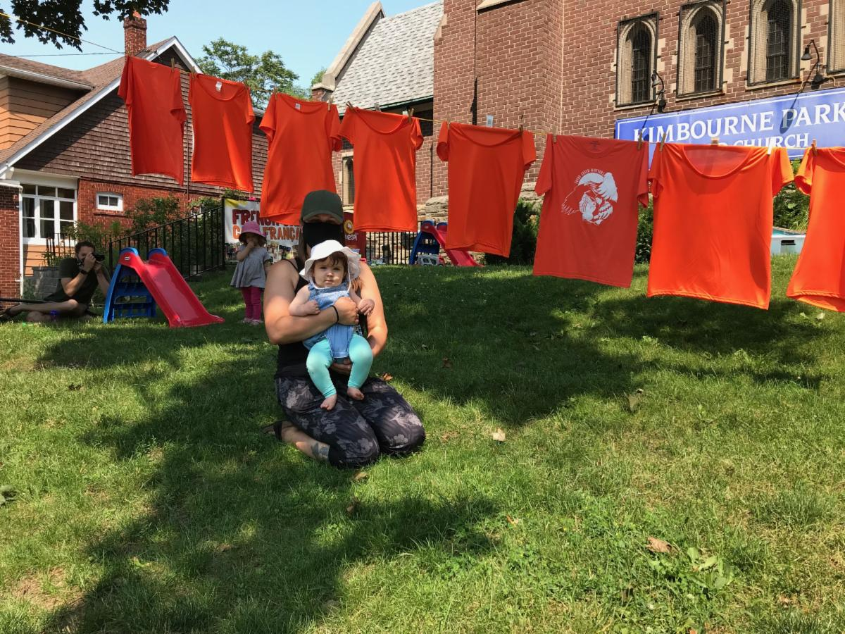 a parent and infant sit on the lawn next to a memorial of orange shirts hanging on a clothesline