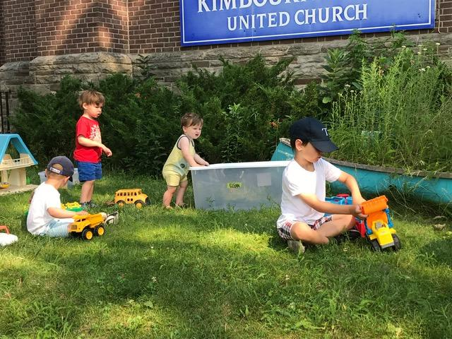 a small group of white children sit on the lawn playing with trucks
