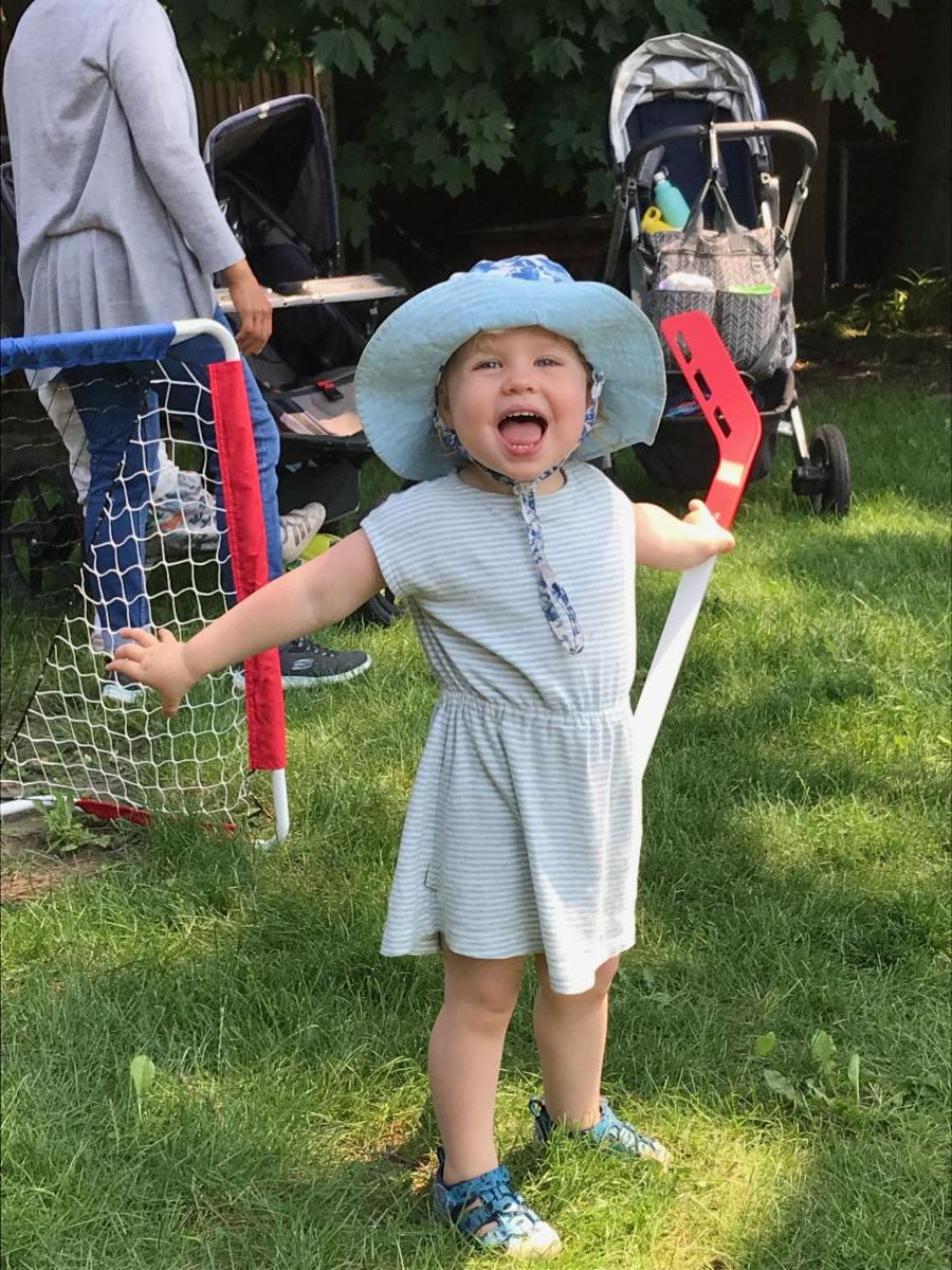 a while child wearing a light blue dress and sunhat holds a plastic hockey stick with their arms spread wide in a cheering gesture