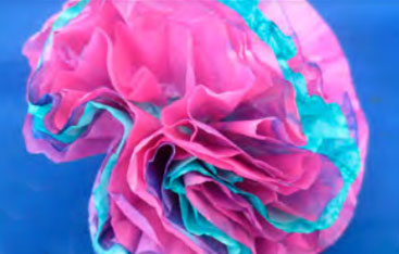layers of coloured paper are gathered to form a paper coral that also looks like a flower