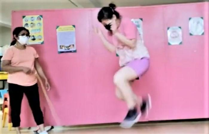 Against a pink background a brown person with dark hair wearing a white facemask holds a skipping rope while an Asian person with dark hair weaing a dark face mask jumps