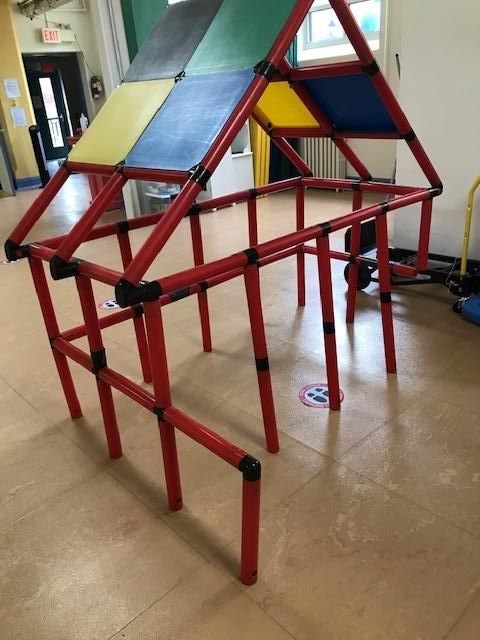 a partially disassembed roof for an indoor climbing structure for children sits on the floor