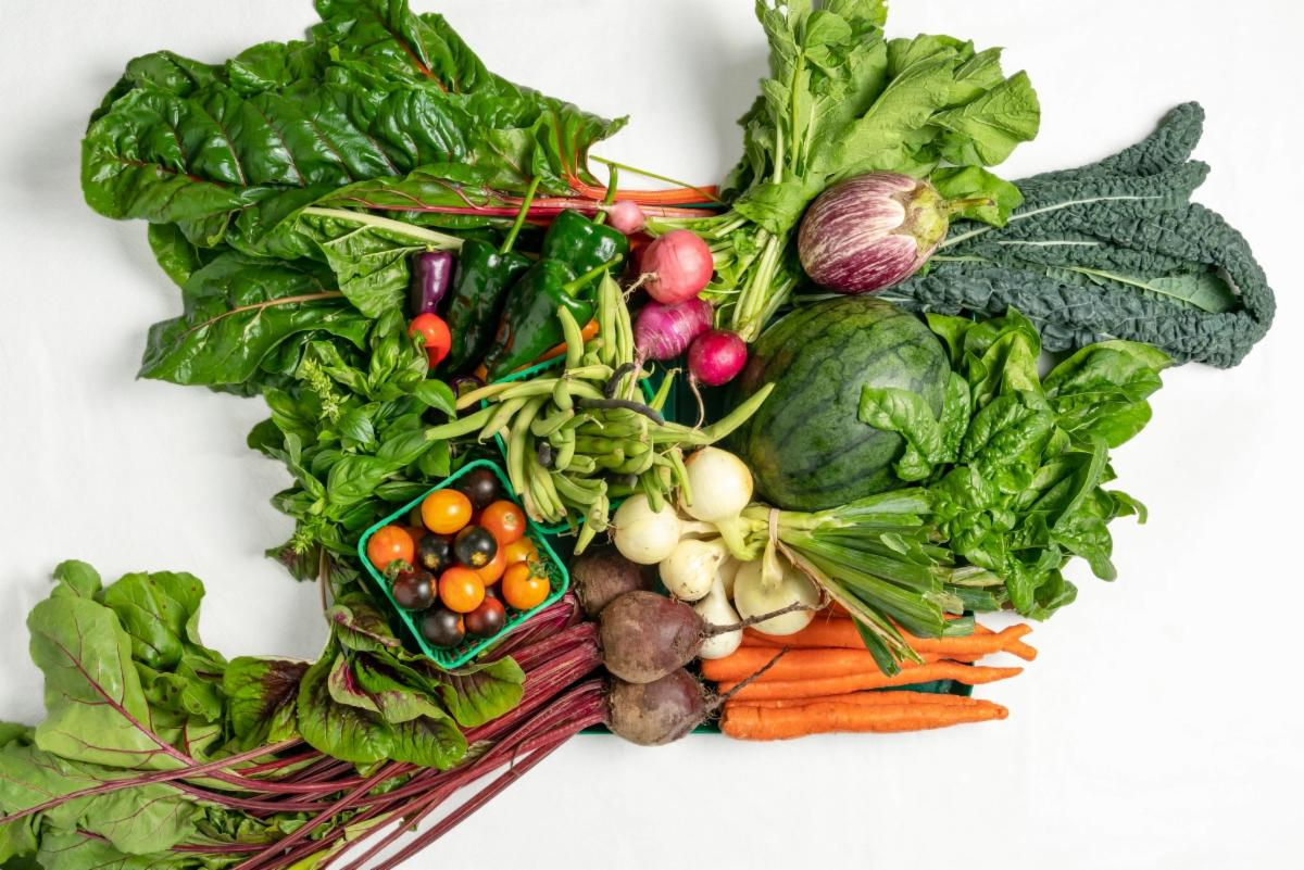 assorted vegetables including carrots and beets and a small box containing multicoloured grape tomatos surrounded by many varieties of leafy greens