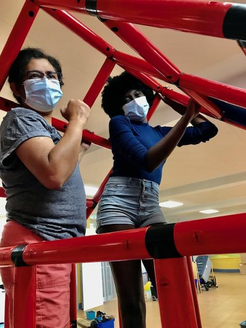 a brown person stands next to a black person both wearing masks and reaching toward the red tubes of the climbing apparatus they are building