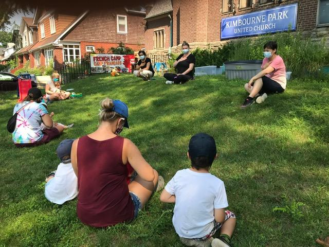 a group of adults with children sit socially distanced on the church lawn singing songs