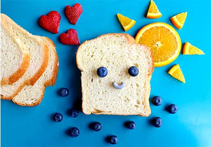 Image of a slice of bread with a smile made of fruit