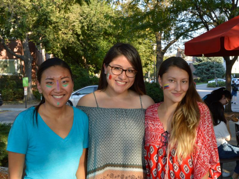 Three female students with cheeks painted at fiesta