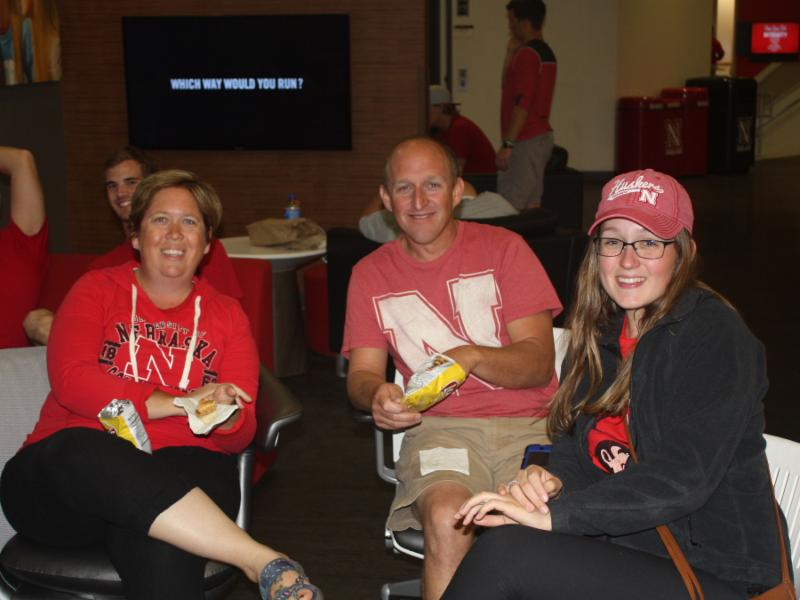 Parents and student smile as they watch the Husker football game together at the Nebraska Union.