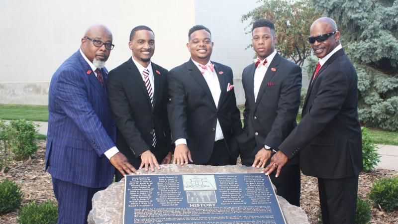Five members of Kappa Alpha Psi fraternity with rock located south of Nebraska Union.