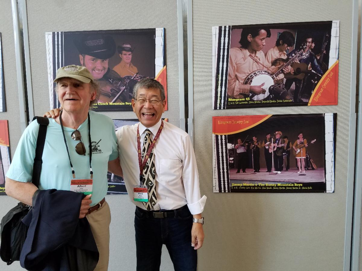 Albert Ihde and Akira Otsuka in front of a photo of The Bluegrass 45