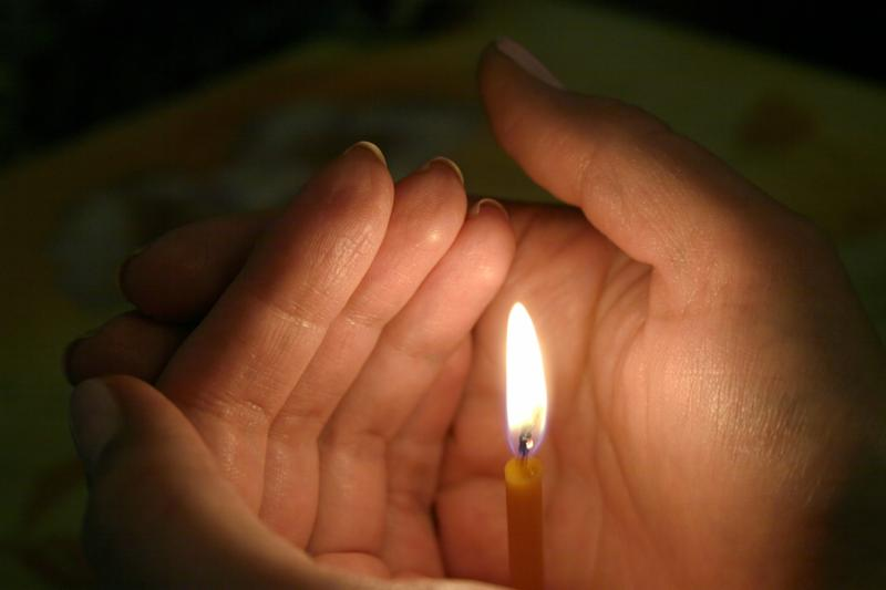 lighting candle in womans hand. dark tone.