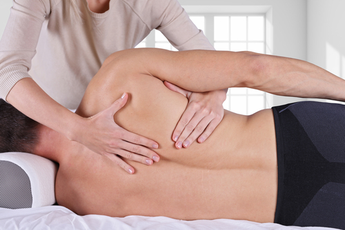 Chiropractic_ osteopathy_ dorsal manipulation. Therapist doing healing treatment on man s back . Alternative medicine_ pain relief concept
