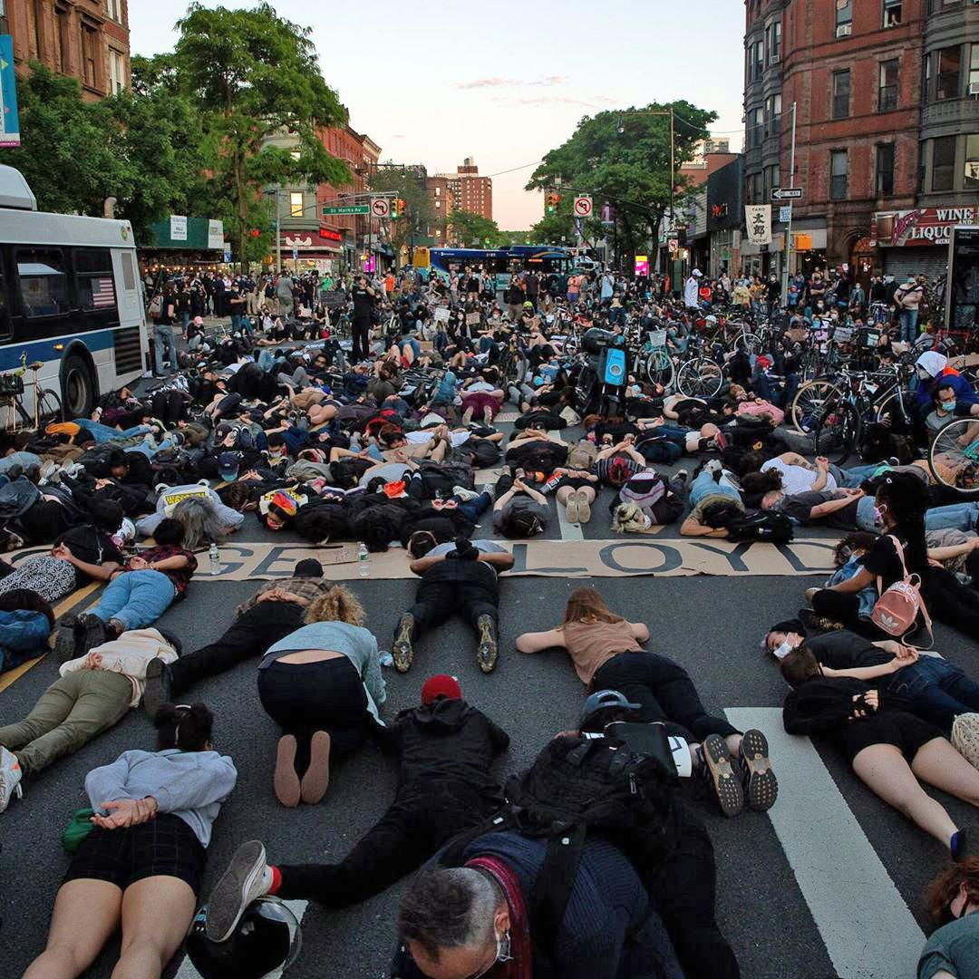 many people laying on the street during a protest