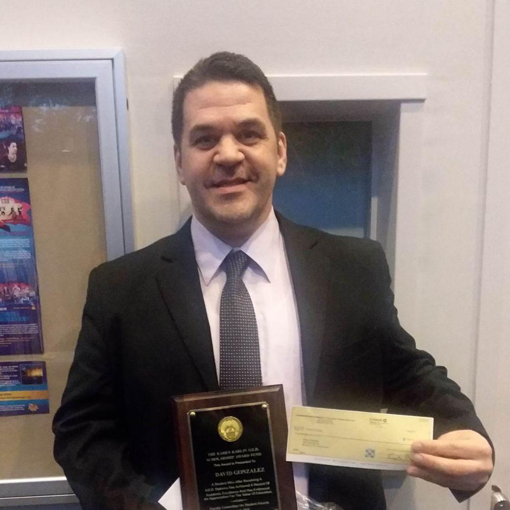 A portrait of David Gonzalez holding an award